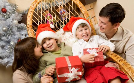 Portrait of happy kids in Santa caps surrounded by their parents Stock Photo - 6091826