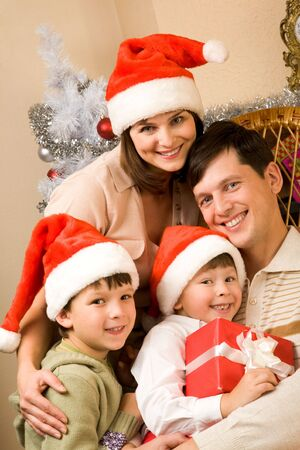Portrait of happy family in Santa caps at home photo
