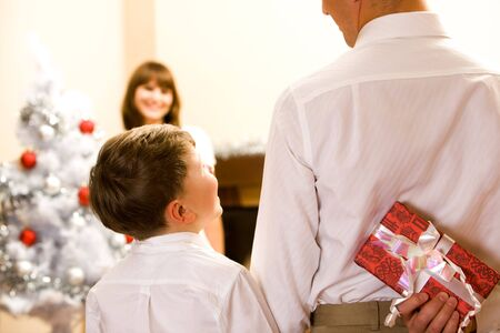 Rear view of man holding giftbox in hand with his son near by photo