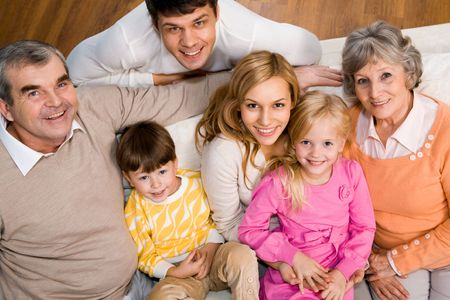 Above shot of senior and young couples with two children sitting on sofa and looking at camera Stock Photo - 6091823