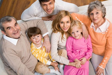 Above shot of senior and young couples with two children sitting on sofa and looking at camera Stock Photo - 6091888