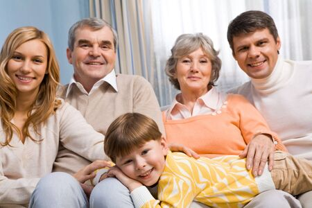 Portrait of cute boy lying on knees of parents and grandparents and looking at camera Stock Photo - 6091894