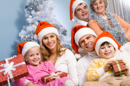 Portrait of happy young couple with two children wearing Santa caps on background of grandparents photo