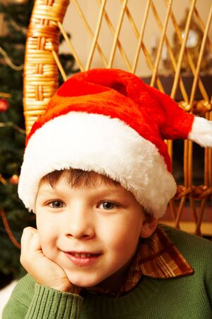 Adorable boy in Santa hat touching his face and smiling photo