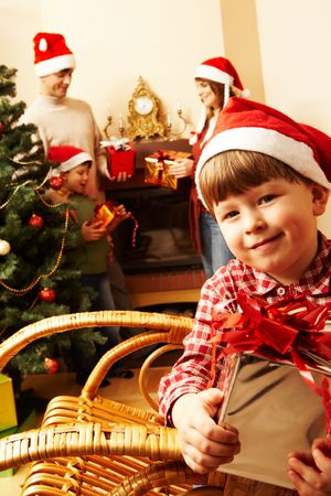 Portrait of joyful little boy holding present on the background of his relatives  photo