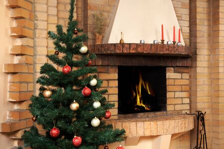 Christmas room with fireplace and decorated fir tree with toys on it photo