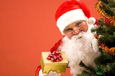 Photo of happy Santa Claus with small giftbox looking at camera out of decorated xmas tree photo