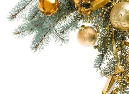 Image of golden toy balls, sweets and beads hanging on spruce branch over white background photo