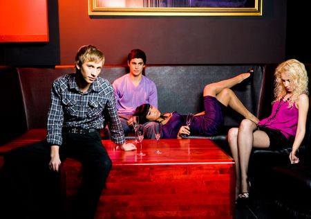 Portrait of group of young people relaxing in night club photo
