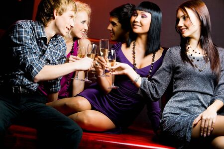 gathering: Portrait of joyful friends toasting with flutes of champagne at party