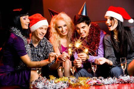gathering: Portrait of laughing friends enjoying xmas lights at new year party Stock Photo