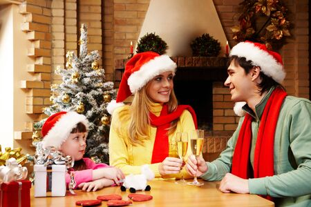 weihnachten: Happy daughter looking at her parents while they cheering up with champagne flutes Stock Photo