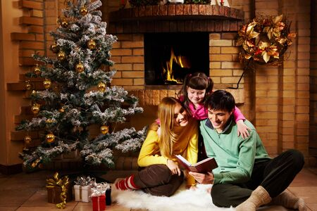 Portrait of cheerful family sitting on white fur reading old book with decorated fir tree near by Stock Photo - 6107027