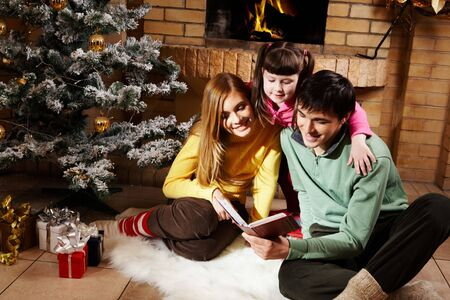 Portrait of friendly family reading old book with decorated fir tree and giftboxes near by photo