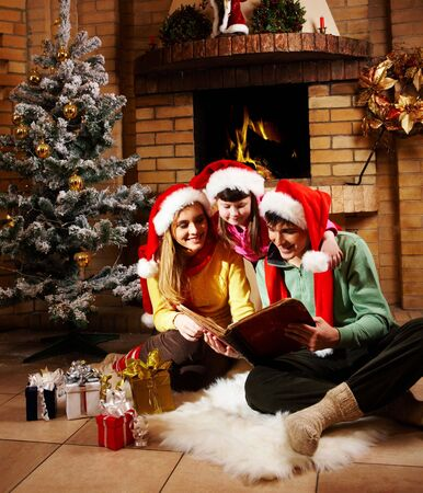Portrait of family spending Christmas evening at reading book by fireplace Stock Photo - 6107028