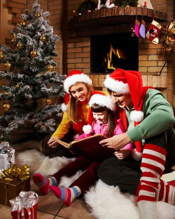fireplace family: Portrait of family reading book by fireplace on Christmas evening Stock Photo