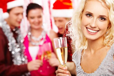 Portrait of beautiful female with champagne looking at camera and smiling photo