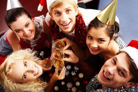 looking upwards: View from above of merry friends with flutes of champagne looking upwards