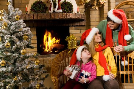 Portrait of happy family in santa caps sitting by fireplace and looking at each other photo