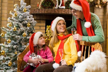 Portrait of happy family in santa caps sitting by fireplace and looking at each other on Christmas Eve Stock Photo - 6107264