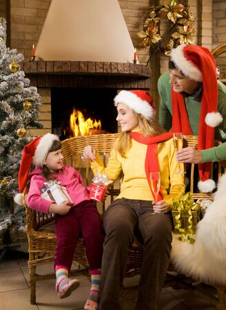 Portrait of happy parents and their cute daughter with presents at home on Chrismas day photo