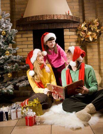 feliz: Ritratto di genitori allegri seduta sulla pelliccia bianca e guardando la ragazza carina durante la lettura del libro antico