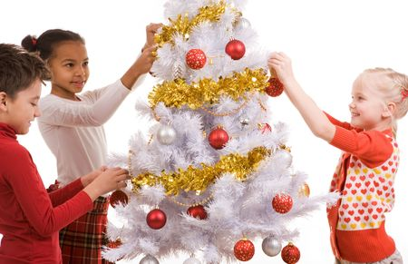 Group of children by the New Year tree decorating it with golden garlands and toy balls photo