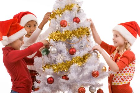 new year eve beads: Group of children by the New Year tree decorating it with golden garlands and toy balls Stock Photo