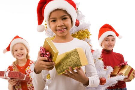 weihnachten: Happy girl with giftbox looking at camera with her friends at background