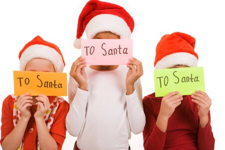 Happy children hiding their faces behind envelopes with note �To Santa� photo
