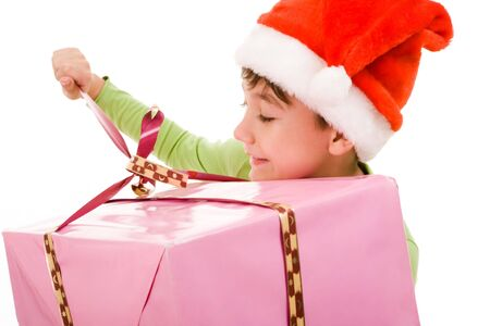 unwrapping: Portrait of boy in Santa cap unwrapping ribbon of smart present
