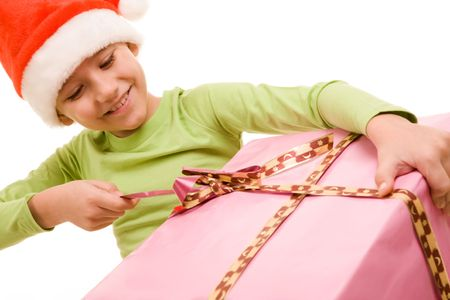 Portrait of boy in Santa cap unwrapping ribbon of smart present photo