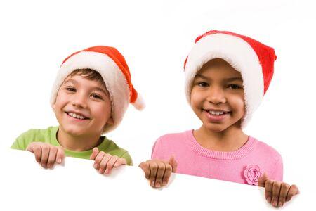 Photo of happy friends in Santa caps smiling at camera photo