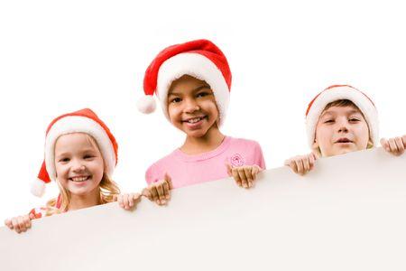 Photo of happy friends in Santa caps peeking into camera photo