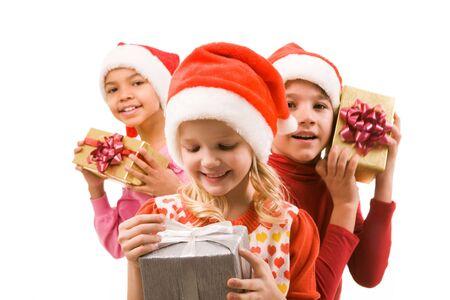 ni�os contentos: Ni�a feliz con giftbox en manos de mirarlo con sus amigos en segundo plano Foto de archivo