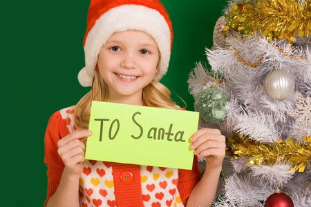 Happy girl holding letter with note �To Santa� with decorated firtree near by photo