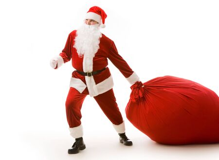 Portrait of happy Santa carrying heavy big red sack with presents photo