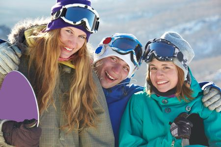 Portrait of happy company of guy and girls in googles laughing photo