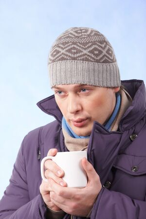 Portrait of young man in warm clothes drinking hot tea or coffee photo