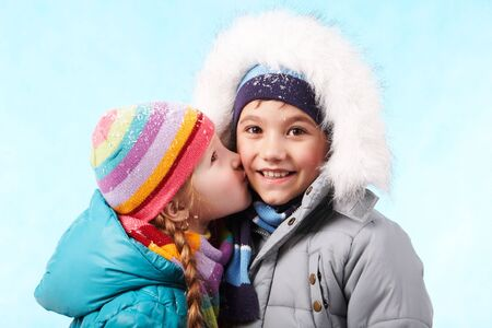 warm jacket: Portrait of happy child smiling at camers while being kissed by pretty girl