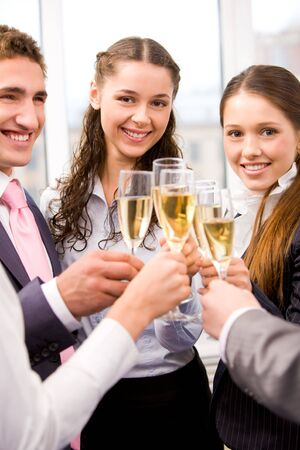 Photo of happy friends holding glasses full of champagne and smiling during party Stock Photo - 6107262
