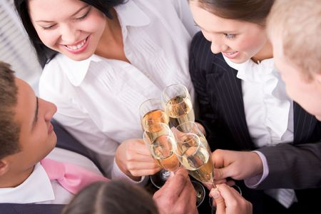 Photo of happy friends holding glasses full of champagne during party photo