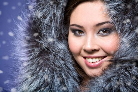Portrait of beautiful female wearing fur cap and smiling photo