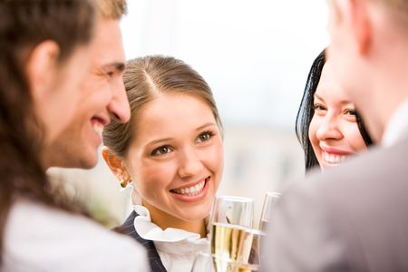Photo of happy woman holding flute with champagne and smiling at her colleagues during party Stock Photo - 6107272