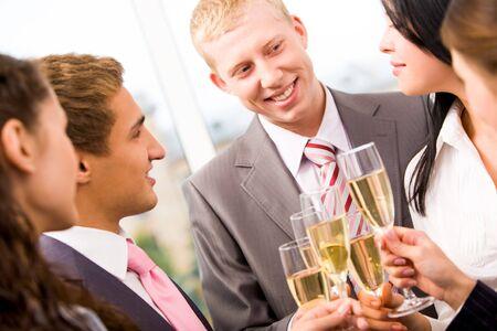 Foto van de fluit van de gelukkige man met champagne en glimlachend op collega's tijdens feest
