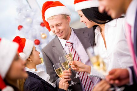 Image of cheering friends in Santa caps making toast at corporate party photo