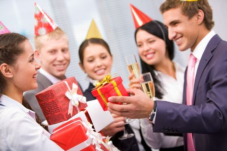 corporate group: Portrait of joyful girl in birthday cap holding heap of giftboxes given by her colleagues