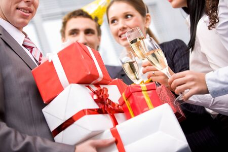 Image of wrapped giftboxes in male hands with cheering friends on background  photo