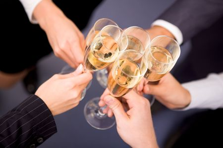 Close-up of human hands cheering up with flutes of golden champagne photo