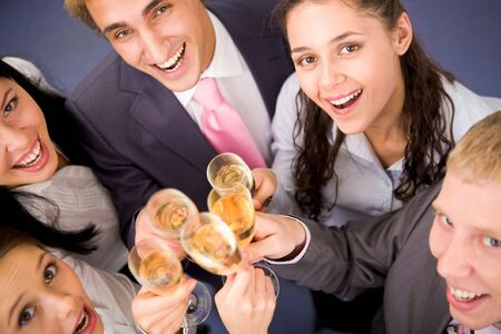 Photo of happy friends cheering up during corporate party photo